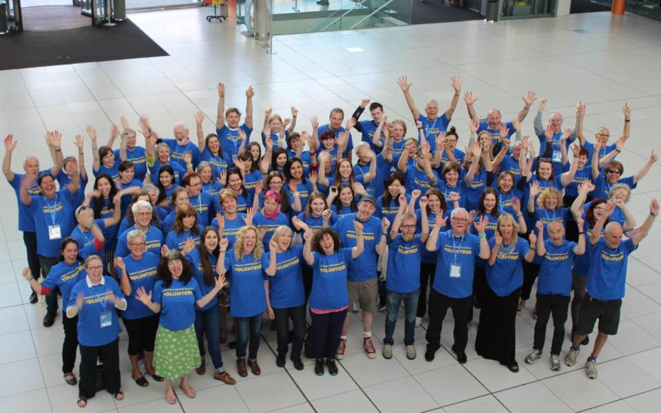 A large group of NNF volunteers with their hands raised in the air.
