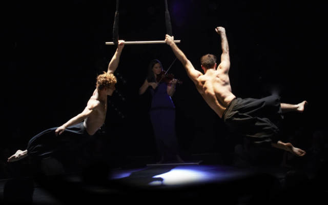 Photo from NNF15 show What Will Have Been, in the background a woman is playing the violin. In the foreground two men hang from a trapeze.
