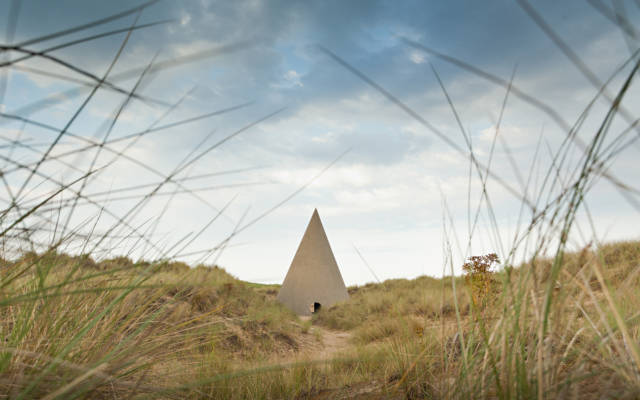 Photo from NNF12 show Walking, a large cone with a spherical door sits on a sand dune.