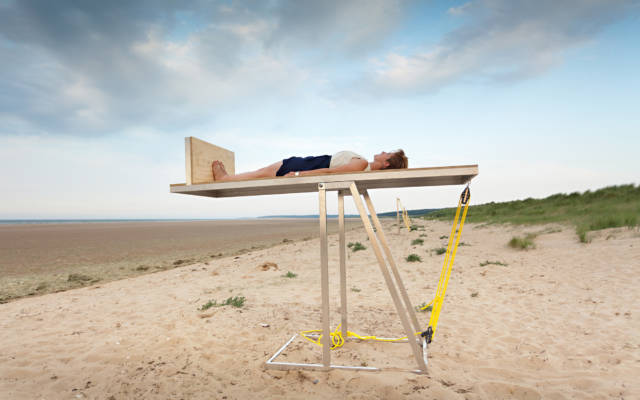 Photo from NNF12 show Walking, a woman lies horizontally on a structure raised above a beach. The sea can be seen on the horizon.