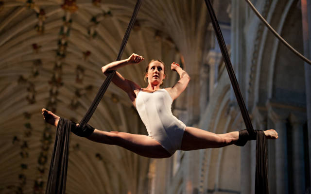 Photo from NNF12 show How Like An Angel, a woman performs the splits in mid-air while hanging from two pieces of silk.