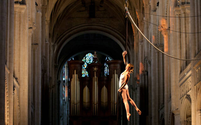 Photo from NNF12 show How Like An Angel, taken in Norwich Cathedral, a woman hangs from a piece of silk, five other performers look up at her from the stage.