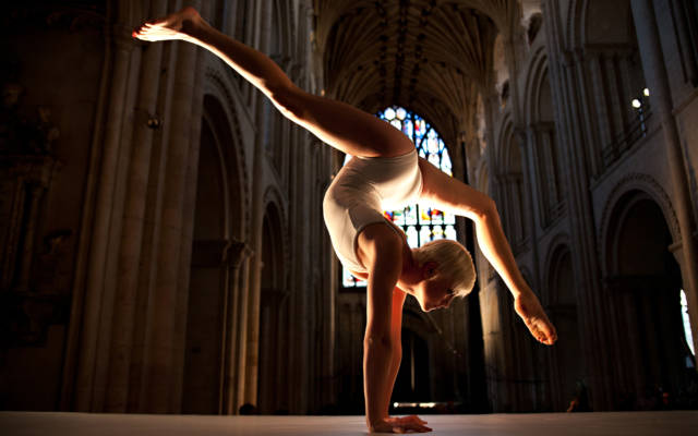 Photo from NNF12 show How Like An Angel, a circus performer stands on her hands with her legs in the air.