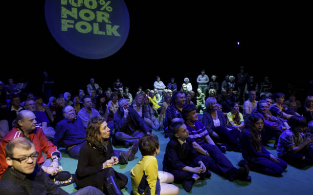 Photo from NNF12 show 100% Norfolk, 100 people sit on stage. The words '100% Norfolk' are projected on the wall behind them.