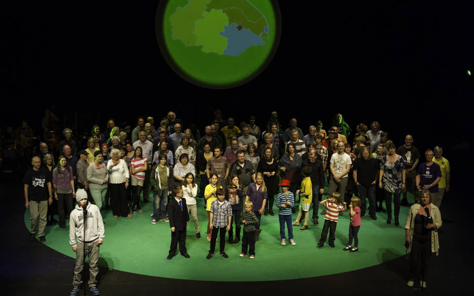 Photo from NNF12 show 100% Norfolk, 100 people stand on a large stage.