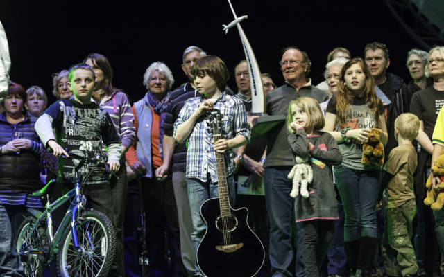 Photo from NNF12 show 100% Norfolk, a large group of people stand on stage, in front is a boy with a bike, another boy with a guitar and a girl with a teddy bear.