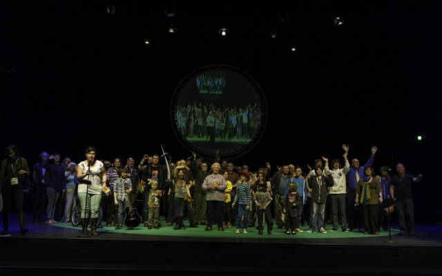 Photo from NNF12 show 100% Norfolk, a group of 100 people of mized ages and genders stand on stage.