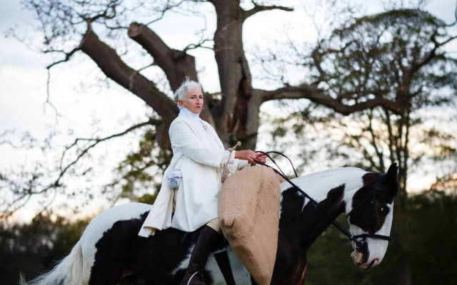 A woman dressed in white rides a black and white horse, a large tree with only a few leave is behind her.