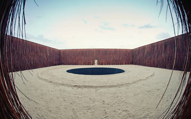 An image taken with a fish-eye lens of a large square structure made with reeds.