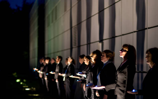 The Voice Project Choir lined up outside the Sainsbury Centre for Visual Arts, they are each holding a blue light in one hand and are illuminated from spotlights in the ground.