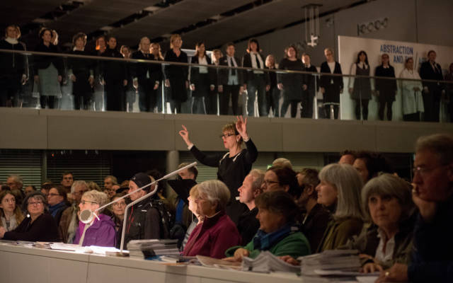 Image taken in the Sainsbury Centre for Visual Arts, The Voice Project Choir stand on the mezzanine and the crowd watch from below.
