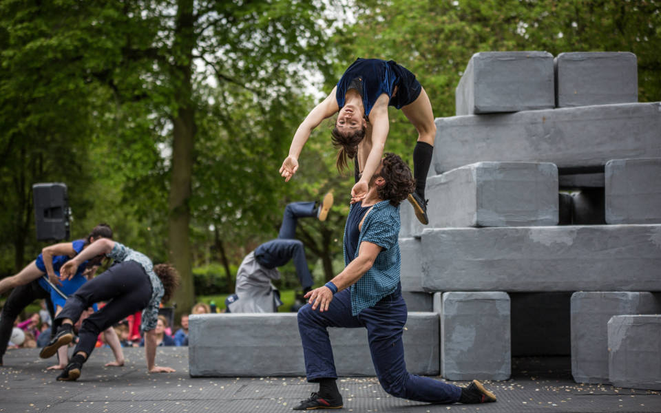Image from an NNF16 show. Lots of large grey blocks are stacked on top of each other on the right side of the picture. A woman is held up by a man who is kneeling in the foreground of the image.