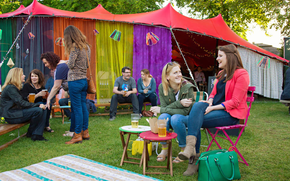 People sitting outside the Adnams Spiegeltent bar in Chapelfield Gardens.