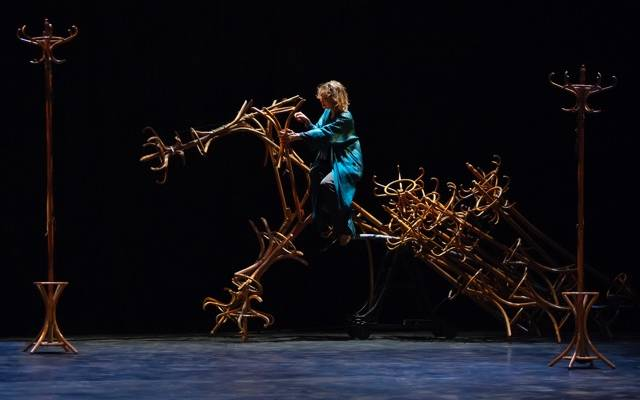 Woman riding a horse made out of coat stands