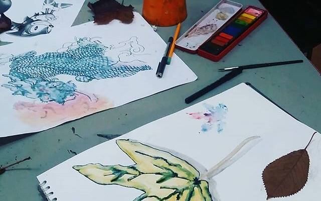 Photo: Work in progress of watercolour paintings with paint pots, brushes and pens on the table