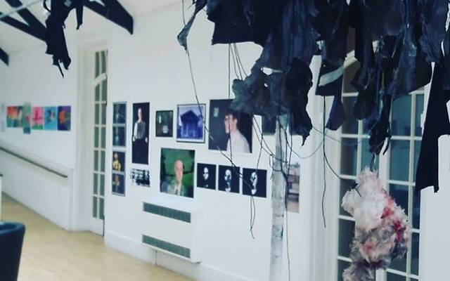 Photo: art gallery, several portraits on a white wall