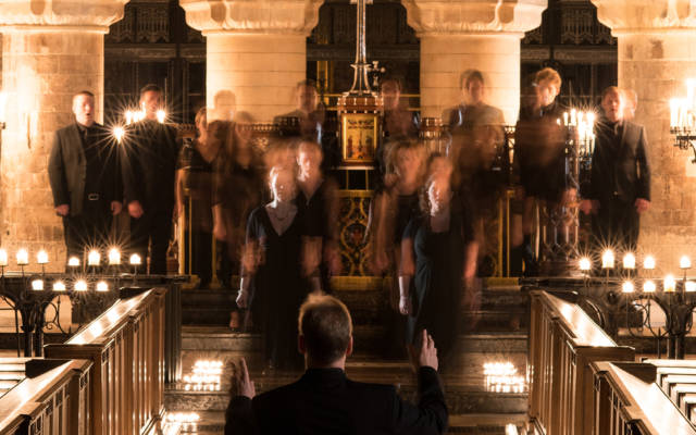 Photo: Tenerae choir in a church, conductor has his back to the camera. Choir is slighlty blurred in a ghostly manner.