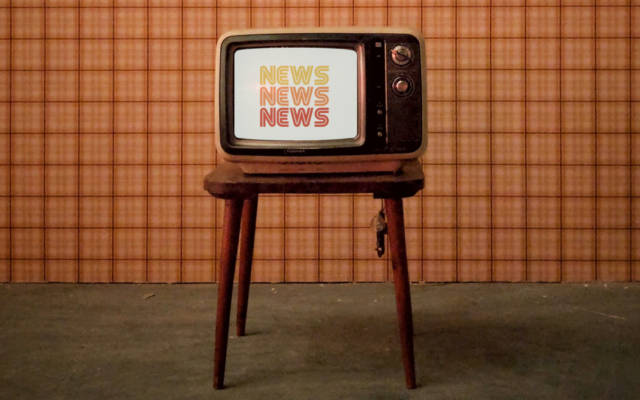 Photo: an old TV on a stool in front of an orange background. News News News logo shown on the TV. 70s style.