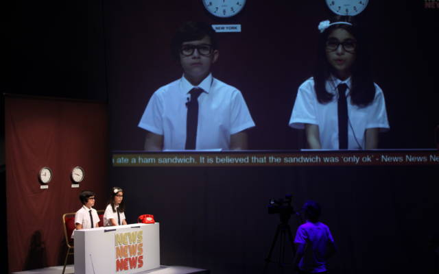 A boy and a girl sitting at a news desk on stage in the lefthand corner. They're shown on a big screen in the middle of the stage.