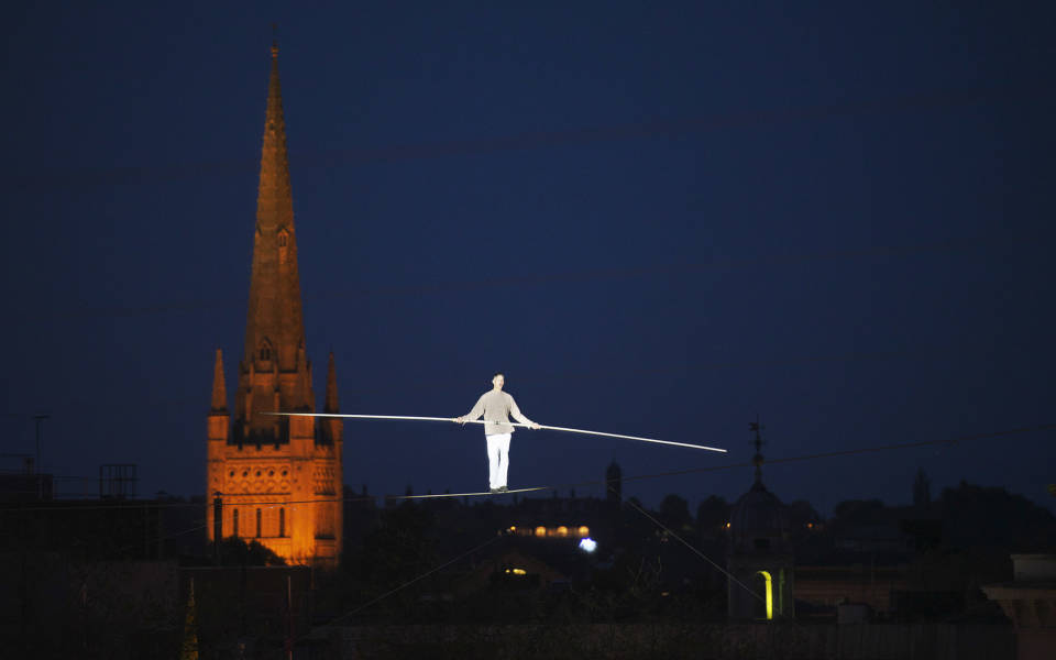 Highwire artist Chris Bullzini walking the highwire, Norwich Cathedral illuminated in the background.