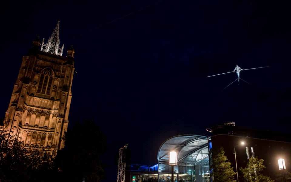 Shot from below: silhouette of Chris Bullzini walking the highwire towards the Forum with St Peter Mancroft Church to his left.